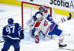 Montreal Canadiens defenseman Joel Edmundson (44) gets tripped as Toronto Maple Leafs forward Joe Thornton (97) looks for the puck during the first period of an NHL hockey game Saturday, May 8, 2021, in Toronto. (Nathan Denette/The Canadian Press via AP)