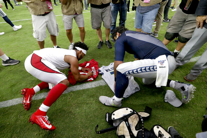 Seattle Seahawks quarterback Russell Wilson, right, and Arizona Cardinals quarterback Kyler Murray, left, exchange jerseys after an NFL football game, Sunday, Sept. 29, 2019, in Glendale, Ariz. (AP Photo/Ross D. Franklin)