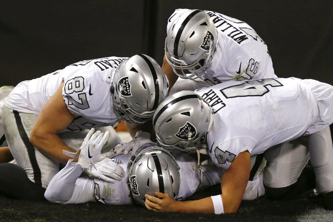 Oakland Raiders running back Josh Jacobs, bottom, is congratulated by teammates after scoring against the Los Angeles Chargers during the second half of an NFL football game in Oakland, Calif., Thursday, Nov. 7, 2019. (AP Photo/D. Ross Cameron)