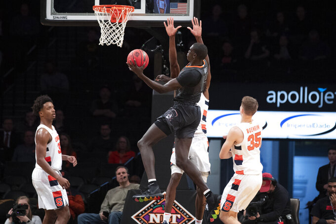 Oklahoma State forward Yor Anei (14) goes to the basket past Syracuse forward Elijah Hughes (33) and guard Buddy Boeheim (35) during the second half of an NCAA college semi final basketball game in the NIT Season Tip-Off tournament, Wednesday, Nov. 27, 2019, in New York. Oklahoma State won 86-72. (AP Photo/Mary Altaffer)