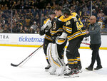 Boston Bruins goaltender Tuukka Rask (40) is helped off the ice after taking a hit on a goal by New York Rangers center Filip Chytil during the first period of an NHL hockey game, Saturday, Jan. 19, 2019, in Boston. (AP Photo/Mary Schwalm)