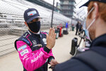 Helio Castroneves, of Brazil, talks with a crew member during testing at the Indianapolis Motor Speedway, Thursday, April 8, 2021, in Indianapolis. (AP Photo/Darron Cummings)