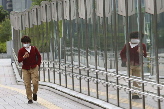 A man wearing a face mask to protect against the spread of the coronavirus walks on a pedestrian overpass in Tokyo, Tuesday, Nov. 24, 2020. (AP Photo/Koji Sasahara)