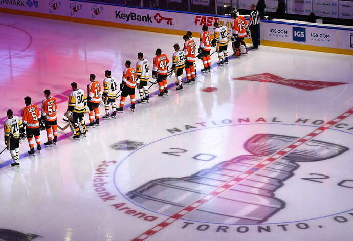 The Pittsburgh Penguins and Philadelphia Flyers line up together for the national anthems before an exhibition NHL hockey game, Tuesday, July 28, 2020 in Toronto. (Nathan Denette/The Canadian Press via AP)