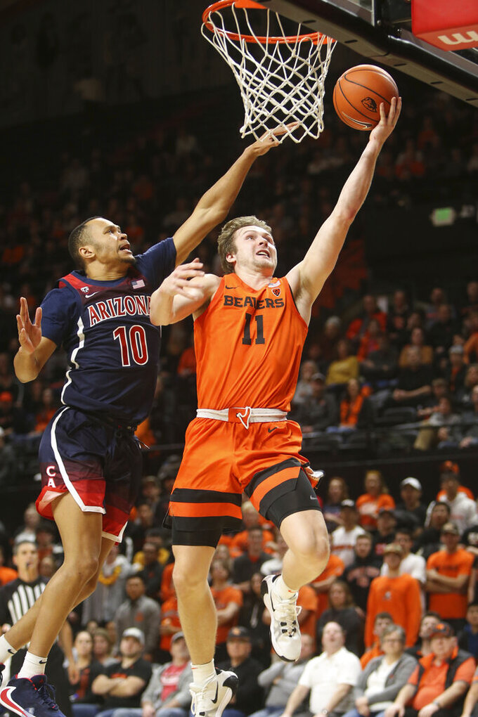 Oregon State's Zach Reichle (11) shoots ahead of Arizona's Jemarl Baker Jr. (10) during the second half of an NCAA college basketball game in Corvallis, Ore., Sunday, Jan. 12, 2020. (AP Photo/Chris Pietsch)