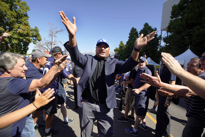 BYU head coach Kalani Sitake greets fans as he arrives before an NCAA college football game against Southern California, Saturday, Sept. 14, 2019, in Provo, Utah. (AP Photo/George Frey)