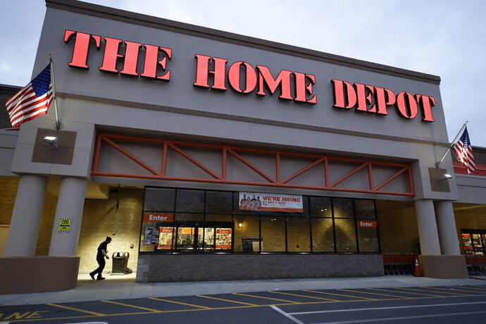 In this Monday, Jan. 27, 2020 photo a passer-by, below left, walks toward an entrance to a Home Depot store location, in Boston. Home Depot Inc. reports financial results on Tuesday, Feb. 25. (AP Photo/Steven Senne)