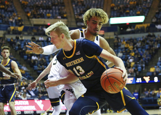 Northern Colorado's Bodie Hume is defended by West Virginia's Emmitt Matthews, Jr. as he goes up court during the first half of an NCAA college basketball game Monday Nov. 18, 2019, Morgantown, W.Va. (AP Photo/Kathleen Batten)