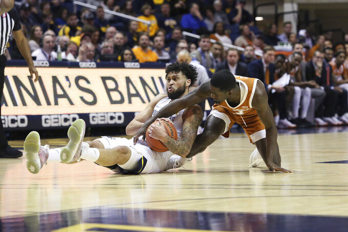West Virginia guard Jermaine Haley (10) and Texas guard Courtney Ramey (3) scramble for a loose ball during the first half of an NCAA college basketball game Monday, Jan. 20, 2020, in Morgantown, W.Va. (AP Photo/Kathleen Batten)