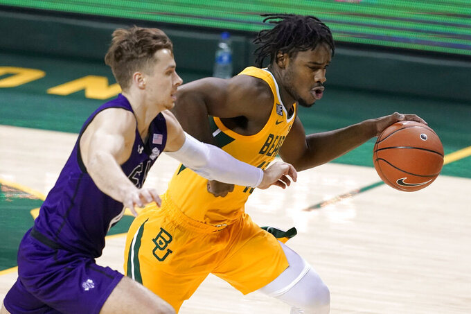 Stephen F. Austin's David Kachelries (4) defends against a drive to the basket by Baylor's Davion Mitchell, right, during the first half of an NCAA college basketball game in Waco, Texas, Wednesday, Dec. 9, 2020. (AP Photo/Tony Gutierrez)