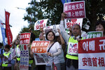 A group of protesters gather outside Japanese Prime Minister Shinzo Abe's residence in Tokyo Thursday, Aug. 8, 2019. They staged a rally with placards to urge the government to apologize for wartime atrocities in an effort fix rapidly souring relations. (AP Photo/Eugene Hoshiko)