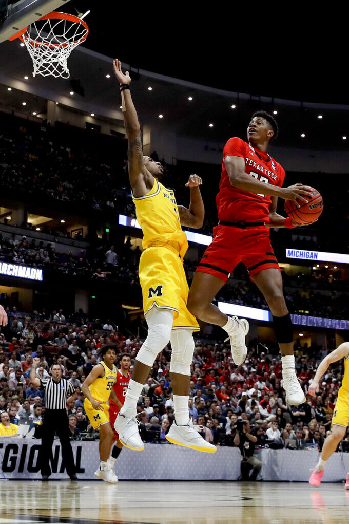 Texas Tech guard Jarrett Culver, right, drives to the basket around Michigan guard Charles Matthews during the first half an NCAA men's college basketball tournament West Region semifinal Thursday, March 28, 2019, in Anaheim, Calif. (AP Photo/Jae C. Hong)