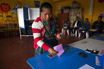 A indigenous woman casts her votes at a polling station in Sumpango, Guatemala, Sunday, June 16, 2019. Guatemalans vote for their next president Sunday in elections plagued by widespread disillusion and distrust, and as thousands of their compatriots flee poverty and gang violence to seek a new life in the United States. (AP Photo/Moises Castillo)