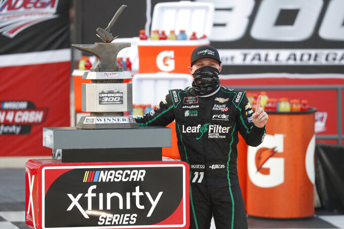 Justin Haley celebrates with the winner's trophy in Victory Lane after winning a NASCAR Xfinity auto race at Talladega Superspeedway in Talladega Ala., Saturday, June 20, 2020. (AP Photo/John Bazemore)