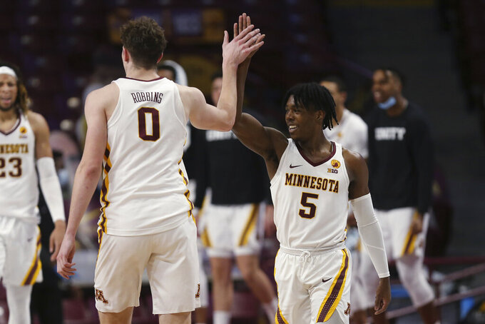 Minnesota's Marcus Carr (5) high-fives teammate Liam Robbins (0) during the second half of an NCAA college basketball game against Michigan State, Monday, Dec. 28, 2020, in Minneapolis. Minnesota won 81-56. (AP Photo/Stacy Bengs)