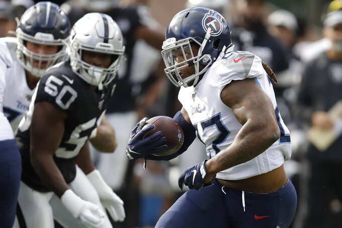 Tennessee Titans running back Derrick Henry, right, runs against the Oakland Raiders during the first half of an NFL football game in Oakland, Calif., Sunday, Dec. 8, 2019. (AP Photo/Ben Margot)