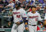 Minnesota Twins' Miguel Sano (22) and Jorge Polanco (11) look down the third base line after the two scored on a C.J. Cron single in the fourth inning of a baseball game against the Texas Rangers in Arlington, Texas, Thursday, Aug. 15, 2019. (AP Photo/Tony Gutierrez)