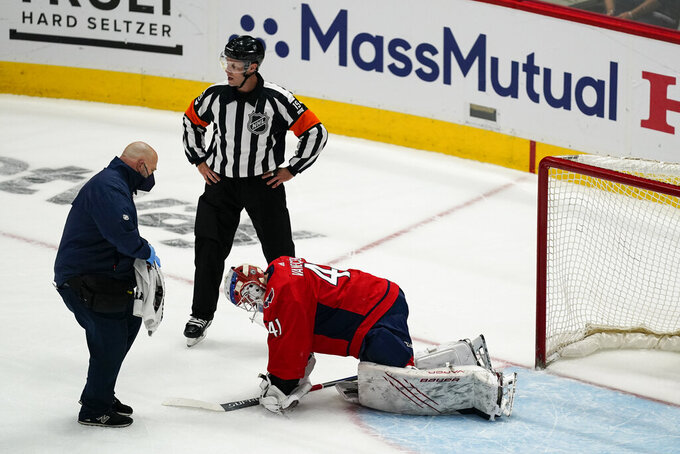 Washington Capitals goaltender Vitek Vanecek (41) receives attention during the first period of Game 1 of th team's NHL hockey Stanley Cup first-round playoff series against the Boston Bruins, Saturday, May 15, 2021, in Washington. Vanecek left the game. (AP Photo/Alex Brandon)