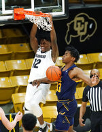 Colorado forward Jabari Walker, left, hangs on the rim after dunking the ball as California forward D.J. Thorpe defends in the first half of an NCAA college basketball game Thursday, Jan. 14, 2021, in Boulder, Colo. (AP Photo/David Zalubowski)