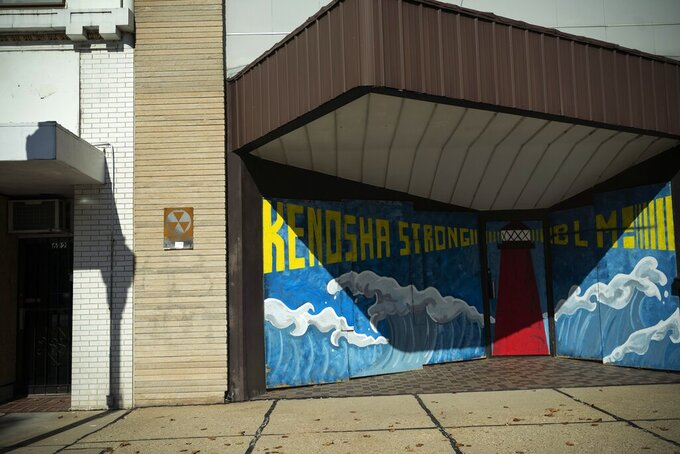 """The windows of a shop front are boarded up with plywood which has a mural that reads """"Kenosha Strong and BLM!"""" painted on it, Friday, Oct. 30, 2020, in downtown Kenosha, Wis. Two months after street violence shook the little lakeside city of Kenosha dozens of businesses are still boarded.  Many of these businesses are open, but with divisive elections just days away some are also hedging their bets, covering up windows and sometimes building outer sets of plywood doors that can be easily shut, like castles pulling up their drawbridges, if trouble returns.   (AP Photo/Wong Maye-E)"""