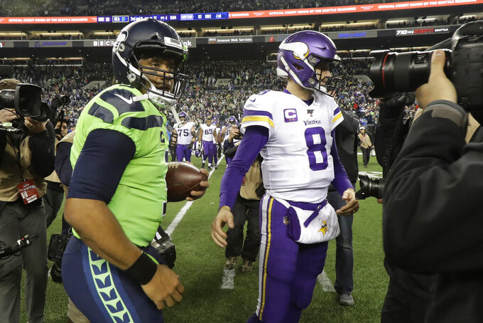 Seattle Seahawks quarterback Russell Wilson, left, greets Minnesota Vikings quarterback Kirk Cousins (8) after an NFL football game, Monday, Dec. 2, 2019, in Seattle. The Seahawks won 37-30. (AP Photo/Ted S. Warren)