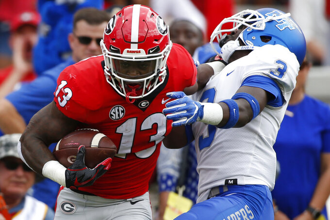 FILE - In this Sept. 15, 2018, file photo, Georgia tailback Elijah Holyfield (13) drives past Middle Tennessee safety Gregory Grate Jr (3) during the first half of an NCAA college football game in Athens, Ga. Georgia rotates running backs effectively and it shows in their yards per carry. Elijah Holyfield has averaged 7.4 yards per rush, DeAndre Swift 4.9, Brian Herrien 6.3 and James Cook 5.5.  (Joshua L. Jones/Athens Banner-Herald via AP)
