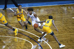 West Virginia guard Mile McBride (4) drives to the basket between two VCU defenders during the first half of an NCAA college basketball game Thursday, Nov. 26, 2020, in SIoux Falls, S.D. (AP Photo/Josh Jurgens)