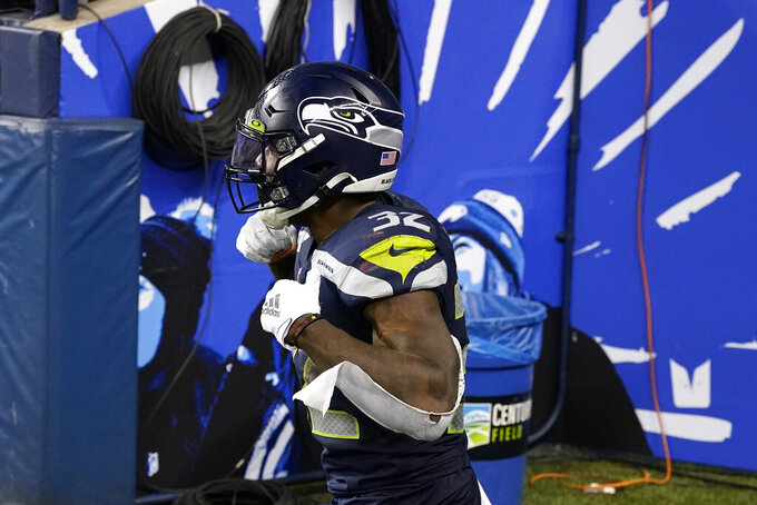 Seattle Seahawks running back Chris Carson celebrates after he caught a pass for a touchdown against the New England Patriots during the second half of an NFL football game, Sunday, Sept. 20, 2020, in Seattle. (AP Photo/Elaine Thompson)