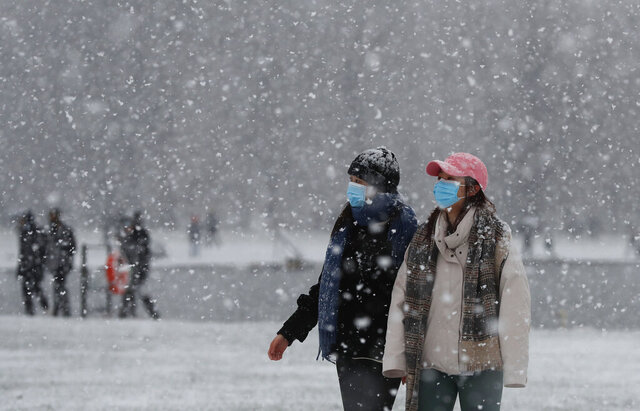 Pedestrians wearing face masks against the coronavirus pandemic walk in Kensington Gardens as snow falls in London, Sunday, Jan. 24, 2021. (AP Photo/Alastair Grant)