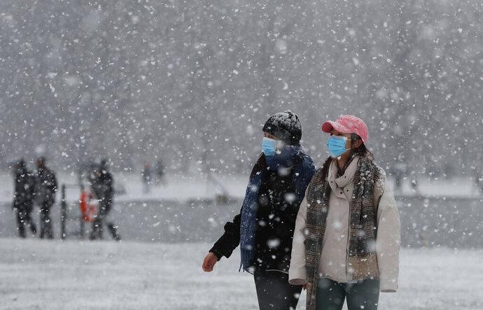Pedestrians wearing face masks against the coronavirus pandemic walk in Kensington Gardens as snow falls in London, Sunday, Jan. 24, 2021. (AP Photo/Alastair Grant)