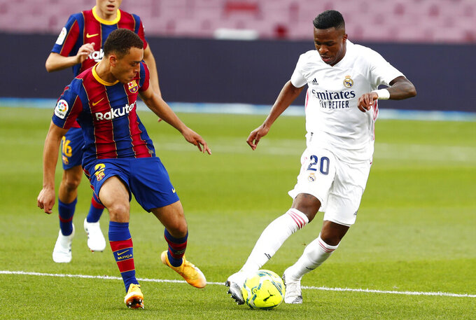 Real Madrid's Vinicius Junior fights for the ball against Barcelona's Sergino Dest during the Spanish La Liga soccer match between FC Barcelona and Real Madrid at the Camp Nou stadium in Barcelona, Spain, Saturday, Oct. 24, 2020. (AP Photo/Joan Monfort)