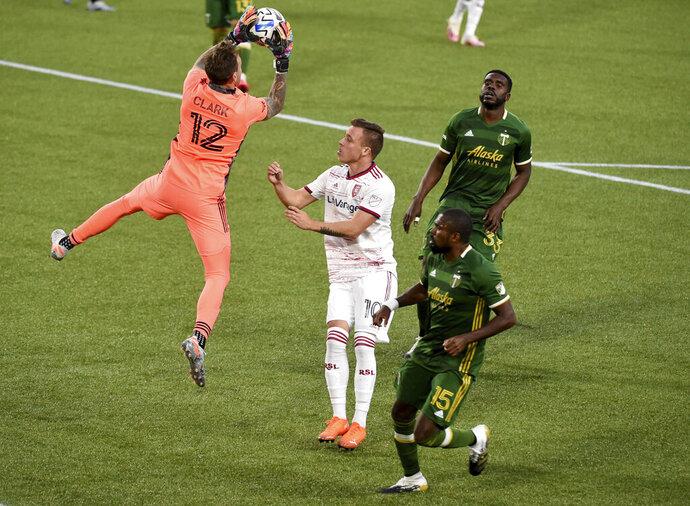 Portland Timbers goalkeeper Steve Clark, left, goes up and grabs a ball in front of Real Salt Lake forward Corey Baird, Center, as Timbers' Chris Duvall, right front, watches during the first half of an MLS soccer match in Portland, Ore., Saturday, Aug. 29, 2020. (AP Photo/Steve Dykes)