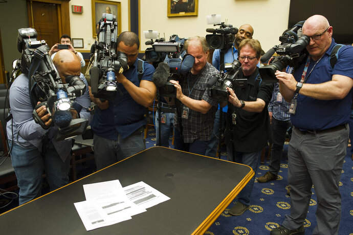 Photojournalists photograph four pages of the Mueller Report laid on the witness table in the House Intelligence Committee hearing room on Capitol Hill, in Washington, Thursday, April 18, 2019. (AP Photo/Cliff Owen)