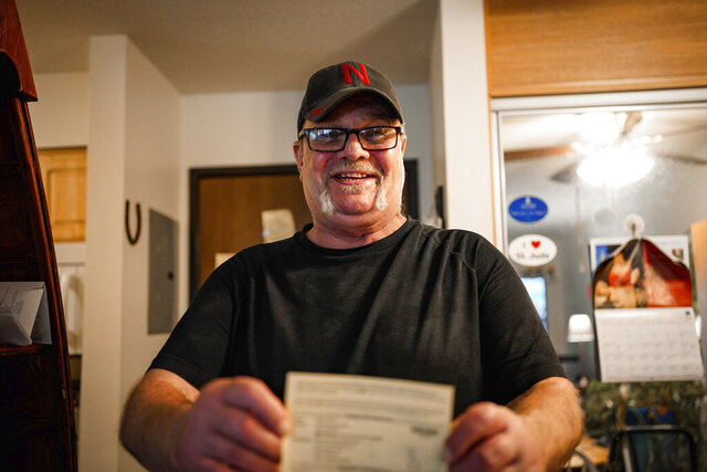 In this undated photo provided by the The ACLU of Nebraska, Wally Wolff holds up voter registration paperwork at his home in Omaha, Neb. The ACLU of Nebraska began sending thousands of notices Monday, Sept. 28, 2020, to felons informing them of their right to vote after learning that the state incorrectly notified Wolff that he wasn't eligible to cast a ballot because of his status as a convicted felon. (Abiola Kosoko/ACLU of Nebraska via AP)