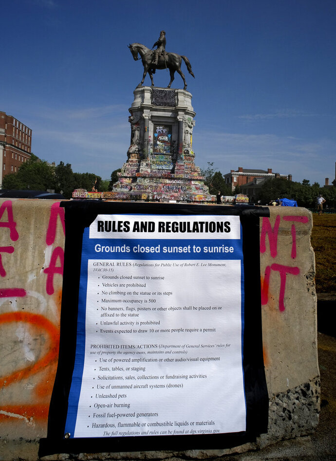 EDS NOTE: OBSCENITY - The new rules and regulations are posted on the barrier surrounding the statue of Robert E. Lee on Monument Ave. in Richmond, Va., Tuesday, June 23, 2020. The area which is a scene of many protests is closed from sunset to sunrise. Gov. Ralph Northam announced plans to remove the Lee statue from the monument, which has become a rallying place for demonstrators in Richmond. (Bob Brown/Richmond Times-Dispatch via AP)