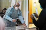 Brant McAdams, left, football coach at Pacific Lutheran, wears personal protective equipment as he prepares COVID-19 tests for student athletes Wednesday, Feb. 3, 2021, on campus in Tacoma, Wash. There was never a chapter in any of the books on becoming a small NCAA college football coach that addressed administering COVID-19 tests in the midst of a pandemic, but now it's something he's doing to give his players the chance at a season. (AP Photo/Ted S. Warren)