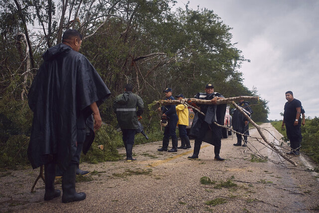 Police clear debris from a road after the passing of Hurricane Delta in Tizimin, Mexico, Wednesday, Oct. 7, 2020. Hurricane Delta made landfall Wednesday just south of the Mexican resort of Cancun as a Category 2 storm, downing trees and knocking out power to some resorts along the northeastern coast of the Yucatan Peninsula. (AP Photo/Andres Kudacki)