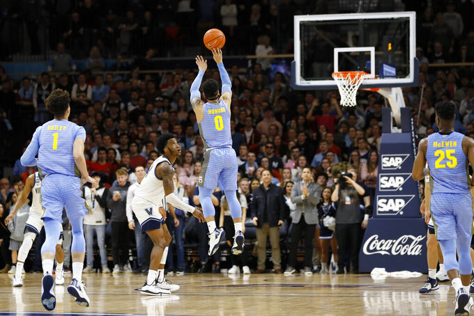 Marquette's Markus Howard (0) goes up for a 3-pointer past Villanova's Saddiq Bey (41) during the final seconds of an NCAA college basketball game Wednesday, Feb. 12, 2020, in Villanova, Pa. (AP Photo/Matt Slocum)