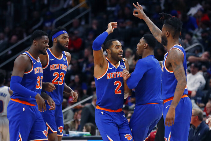 New York Knicks guard Wayne Ellington (2) and teammates celebrate their win over the Detroit Pistons in an NBA basketball game, Saturday, Feb. 8, 2020, in Detroit. (AP Photo/Carlos Osorio)