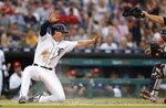 Detroit Tigers' Brandon Dixon, left, signals after safely beating the throw to Boston Red Sox catcher Sandy Leon to score from first on a double by Tigers' Jeimer Candelario during the fourth inning of a baseball game, Friday, July 5, 2019, in Detroit. (AP Photo/Carlos Osorio)