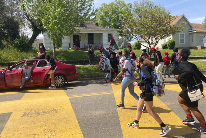 In this April 27, 2021 photo, students walk out of school at Austin-East Magnet High School in Knoxville, Tenn. Members of the Black community in Knoxville, Tennessee, are calling for reforms to dispel longstanding disparities between Blacks and whites. They say that is one of the steps that needs to be taken to reduce increasing violence that has claimed the lives of five high school-age students this year. (AP Photo/Kimberlee Kruesi)