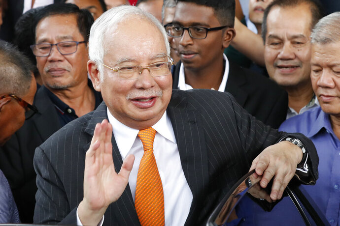 Former Malaysian Prime Minister Najib Razak waves as he leaves Kuala Lumpur High Court in Kuala Lumpur, Monday, Nov. 11, 2019. A Malaysian judge on Monday ordered Najib to enter a defense at his first corruption trial linked to the multibillion-dollar looting at the 1MDB state investment fund that helped spur his shocking election ouster last year. (AP Photo/Vincent Thian)