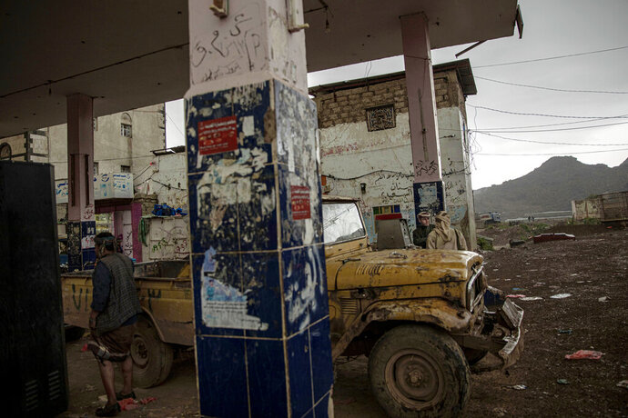 In this Aug. 4, 2019 photo, Yemeni men stop at a gas station in Dhale province, an active frontline between militiamen backed by the Saudi-led coalition and Houthi rebels, where African migrants cross to continue their journey in Yemen. According to the U.N.'s International Organization for Migration, 150,000 arrived in Yemen from the Horn of Africa in 2018, a 50% jump from the year before. The number in 2019 was similar. They dream of reaching Saudi Arabia, and earning enough to escape poverty by working as laborers, housekeepers, servants, construction workers and drivers. (AP Photo/Nariman El-Mofty)