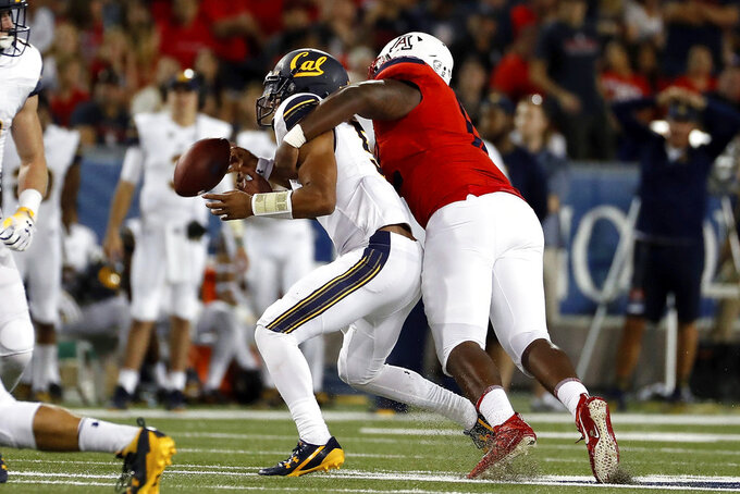 Arizona defensive end JB Brown (12) knocks the ball away from California quarterback Brandon McIlwain (5) during the second half of an NCAA college football game Saturday, Oct. 6, 2018, in Tucson, Ariz. (AP Photo/Chris Coduto)