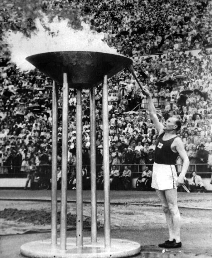 Runner Paavo Nurmi, of Finland, lights the Olympic flame from the Olympic torch, during July 19, 1952, opening ceremony in Helsinki, Finland. (AP Photo)