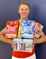 In this image provided by Three Wishes Foods, Syracuse's Buddy Boeheim poses with Three Wishes Foods cereal boxes on Wednesday, July 14, 2021, in DeWitt, N.Y. A new era in college sports got underway at the beginning of July, and with players now allowed to make money on their celebrity it's anybody's guess where this is all headed. Boeheim, the sharp-shooting son of Syracuse men's basketball coach Jim Boeheim, inked a deal that will put his likeness on the front of a cereal box with him shooting, a morsel of Three Wishes cereal in his right palm. (Scott Yager/Three Wishes Foods via AP)