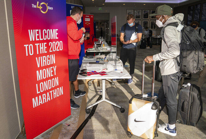 In this image issued by London Marathon Events, Kenya's Eliud Kipchoge registers at the official hotel and biosecure bubble in London, Monday Sept. 28, 2020, ahead of the elite-only 2020 London Marathon on Sunday Oct. 4. The 40th Race will take place on a closed-loop circuit around St James's Park in central London. (Bob Martin/London Marathon Events via AP)