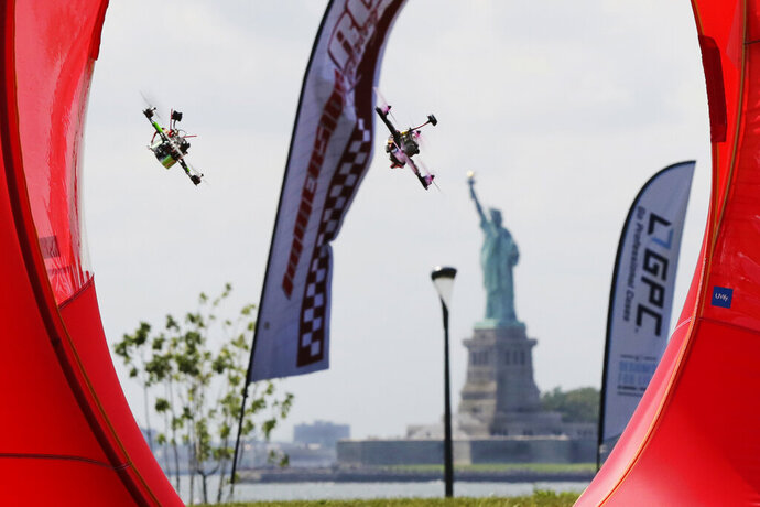 FILE - Pilots fly their small racing drones through an obstacle course for the National Drone Racing Championship on Governors Island, a former military installation in New York Harbor, Friday, Aug. 5, 2016. A major sports book is taking bets on aerial drone races. DraftKings said Friday it is taking bets for the championship this weekend of the Drone Racing League, in which pilots fly aerial drones in races against each other. (AP Photo/Richard Drew, File)
