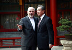 Iranian Foreign Minister Mohammad Javad Zarif, left, gestures as he speaks with his Chinese counterpart Wang Yi during their meeting at the Diaoyutai State Guesthouse in Beijing Tuesday, Feb. 19, 2019. (How Hwee Young/Pool Photo via AP)