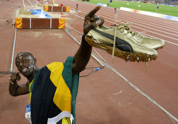 """File- Jamaica's Usain Bolt celebrates winning his third gold medal after the men's 4x100-meter final during the athletics competitions in the National Stadium at the Beijing 2008 Olympics in Beijing, Friday, Aug. 22, 2008. The Olympics are remembered for the stars. That was true in Beijing in 2008, and the stars were Michael Phelps and Bolt. But Beijing is also storied for its signature venues like the """"Bird's Nest"""" stadium, and the """"Water Cube"""" swimming venue. No Olympics before — or since — have impacted a city the way the Olympics did Beijing. (AP Photo/David J. Phillip, File)"""